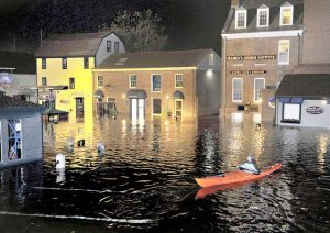 Associated Press Jim Davis kayaks through waters flooding Bowen's Wharf in October 2012 after Superstorm Sandy in historic Newport, R.I