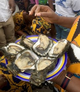 In a circled of onlookers, a woman holds a plate of shucked oysters.