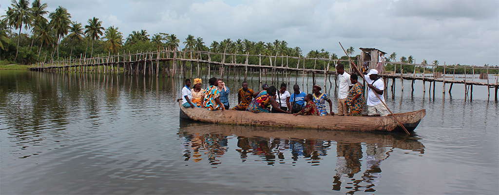 A canoe filled with people poles out from shore