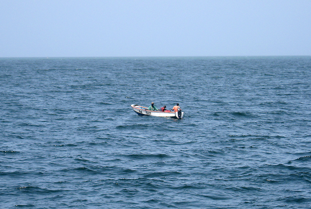 3 fishermen in a small boat in the distance
