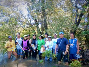 Group line-up photo of Filippinos standing in mangrove estuary