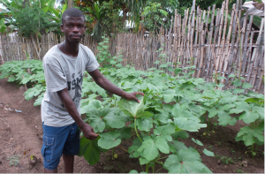 Standing man shows his vegetable patch